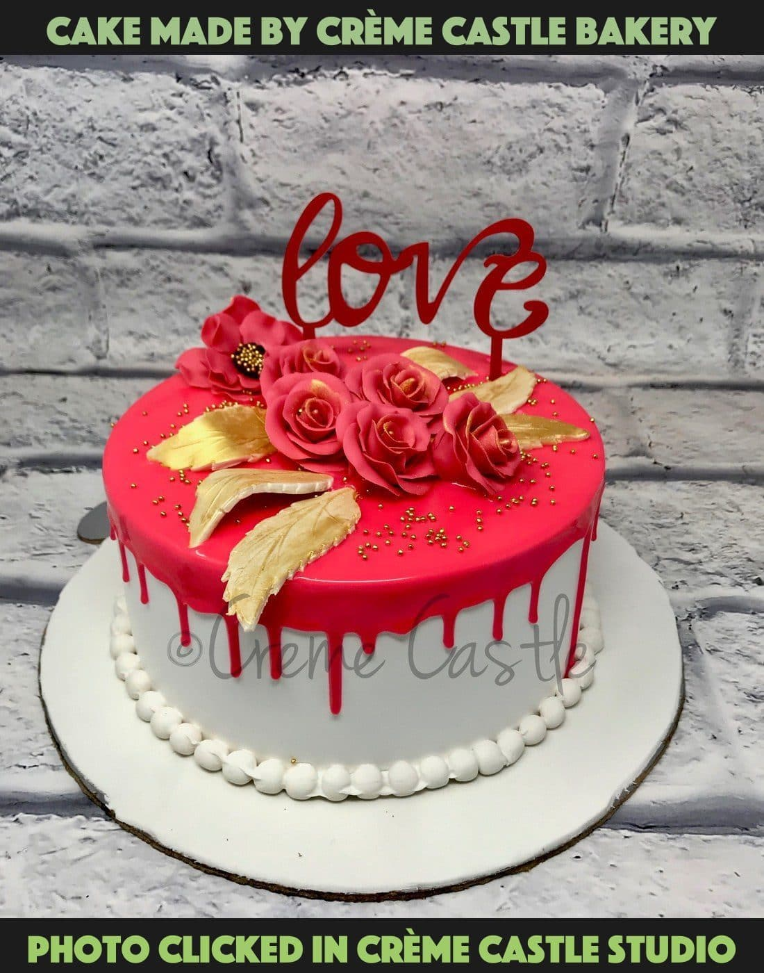 A pink drip cake with roses on top with golden leaves on white base