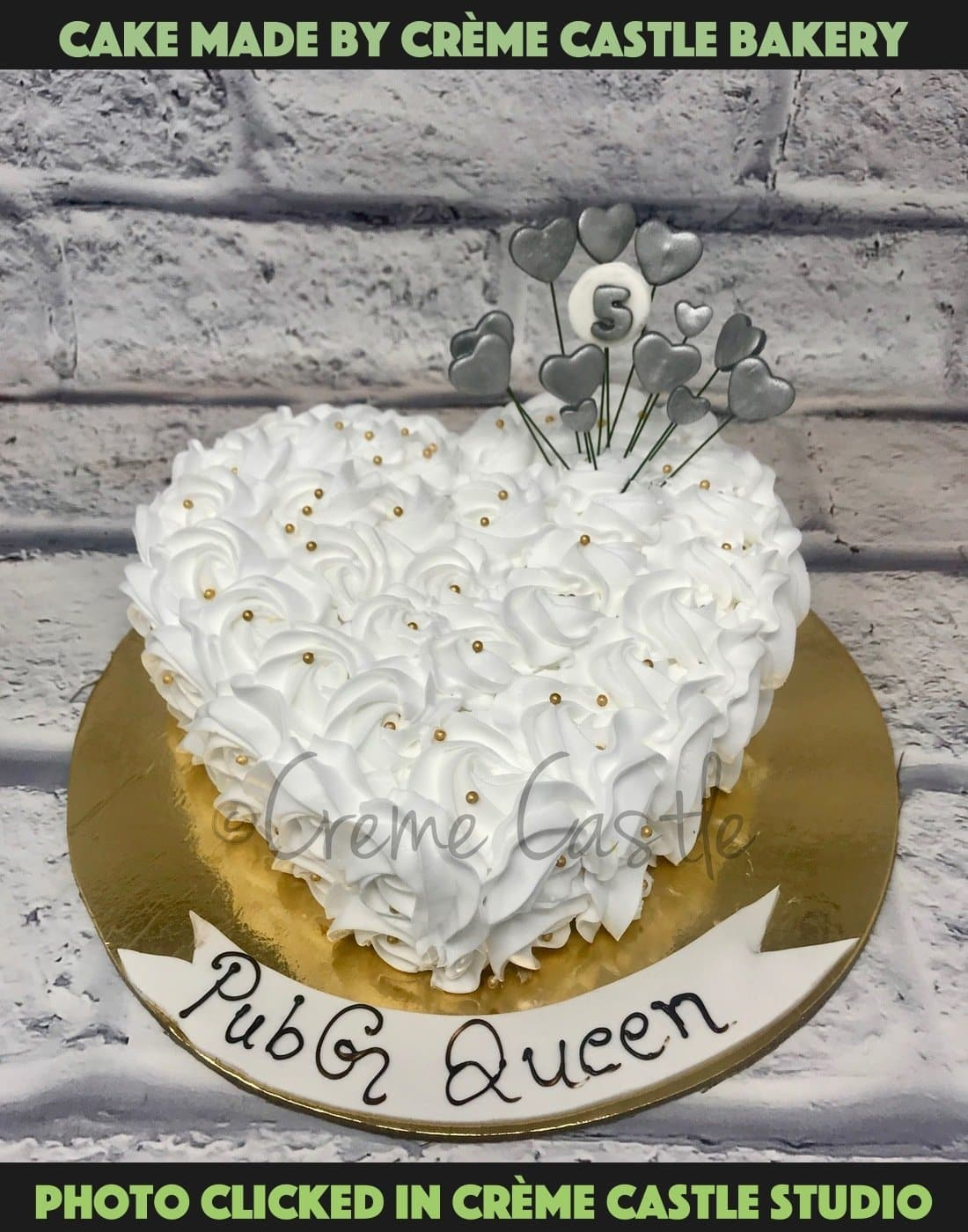 A heart shaped cake covered with white roses made from cream and silver hearts