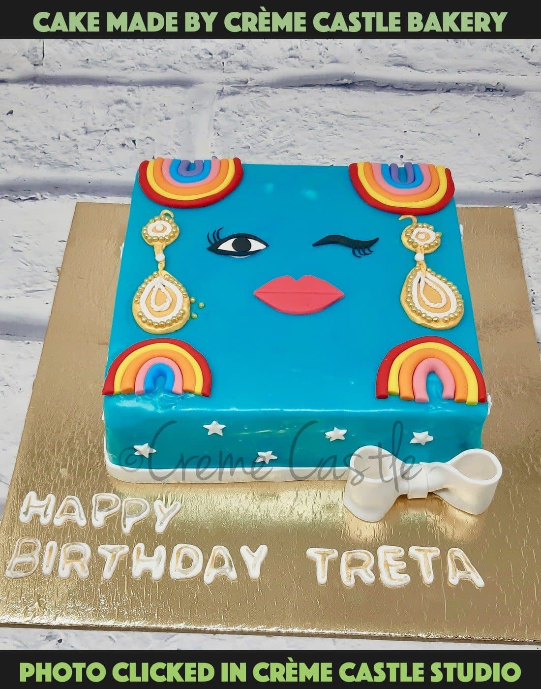 A square cake in blue color with face at the top making a wink!