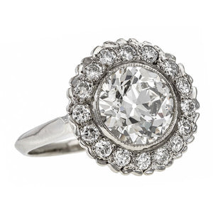Vintage ring: a White Gold Cluster Old European And Round Brilliant Cut Diamond Engagement Ring sold by Doyle & Doyle vintage and antique jewelry boutique.