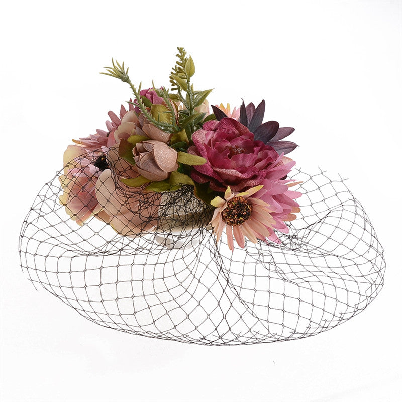 Pink flower fascinator with black cage veil
