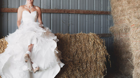 bride sitting on a hay bale at her barn wedding