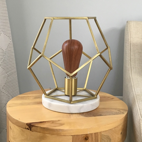 Living room table lamp in brass with statement light bulb.
