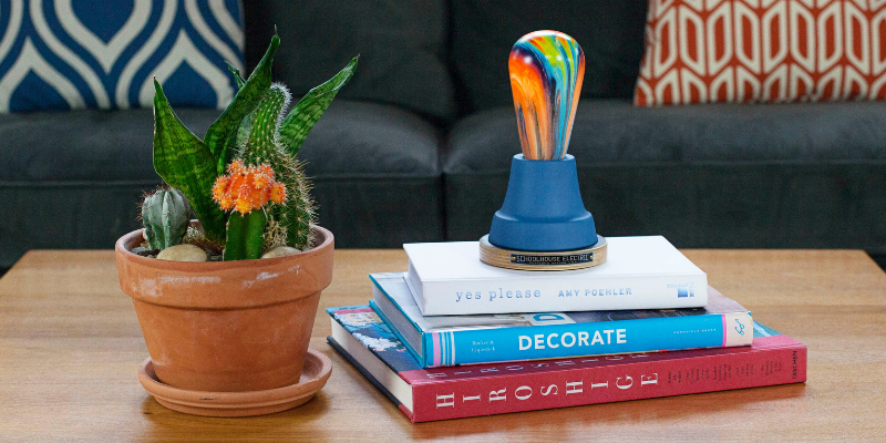 Colorful coffee table decor featuring table lamp, printed bulb and cactus.