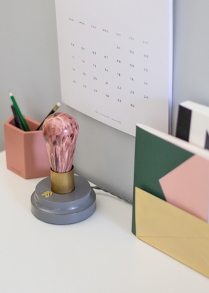 Modern desk decor featuring gray table lamp and wit and delight accessories