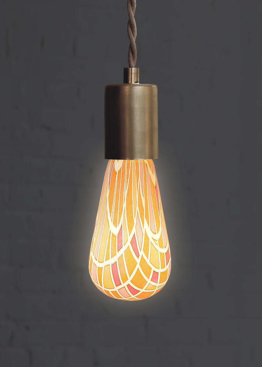 Pink and orange geometric decorative light bulb turned on