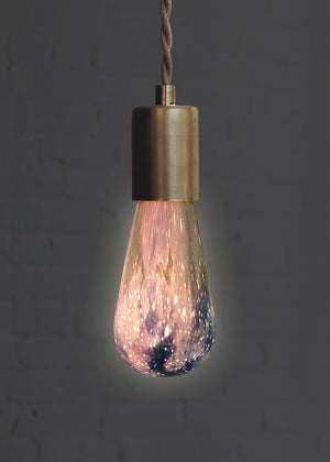 Cool space light bulb in brass pendant turned on