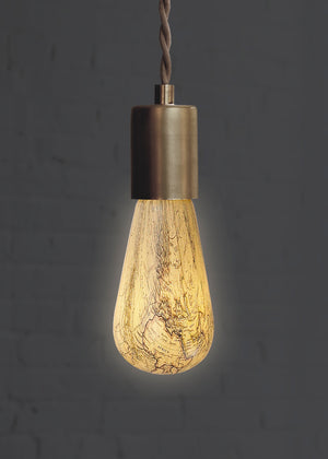 Vintage map light bulb in brass rope pendant turned on