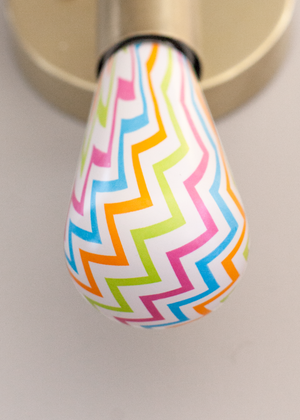 Colorful chevron light bulb in wall sconce fixture