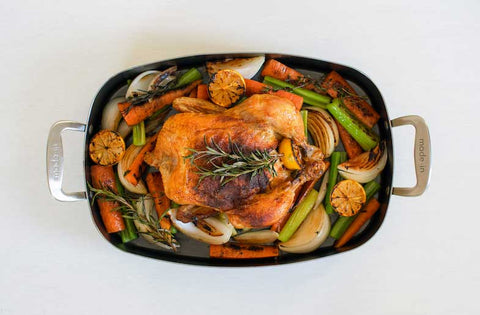 roast chicken and vegetables in a roasting pan