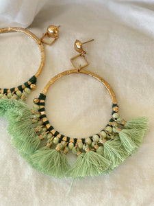 Large gold hoops with light green tassels