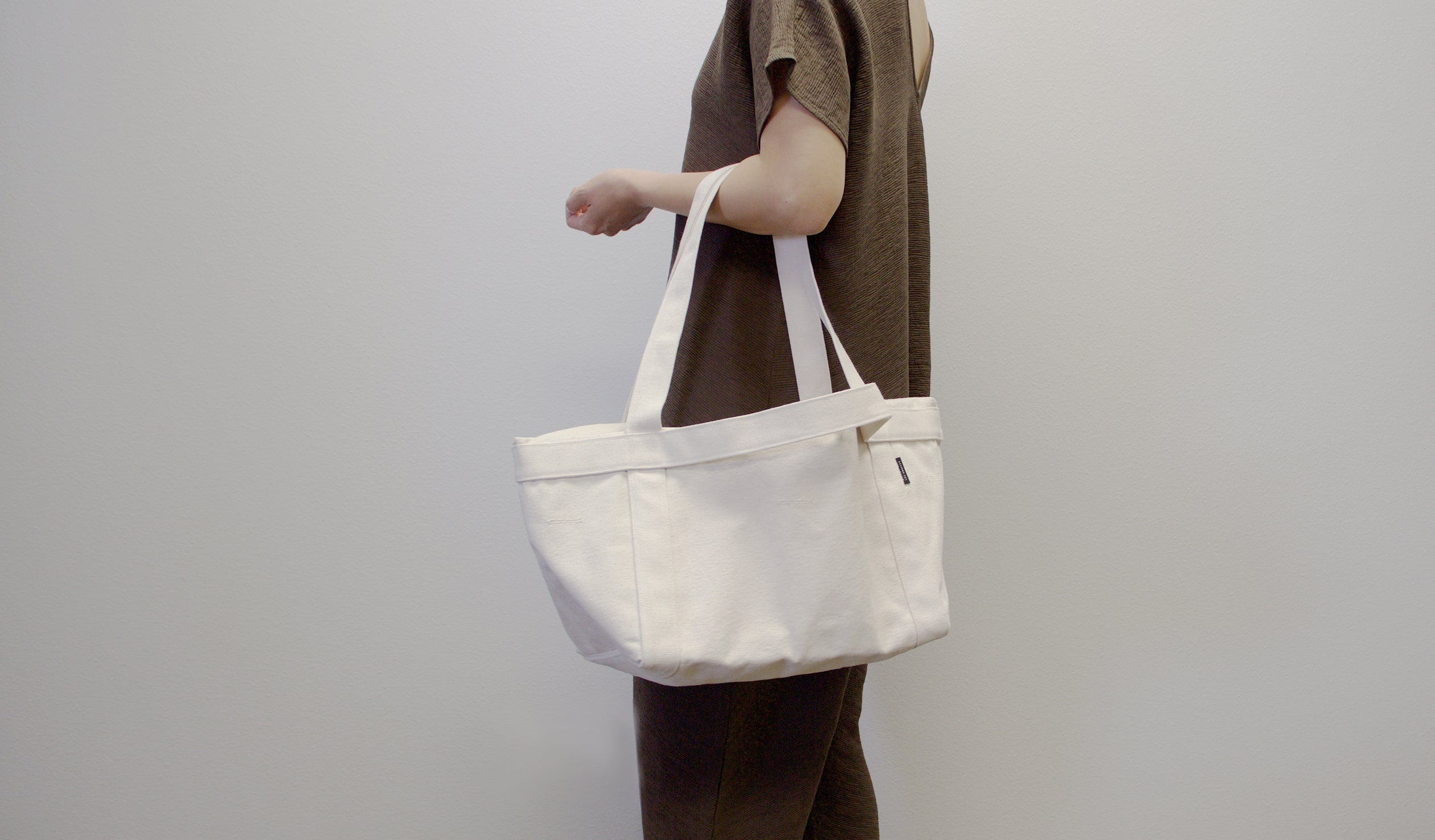 model holding grand day tote in natural color