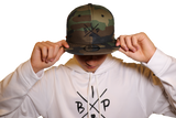 "IBP ""X"" LOGO EMBROIDERED NEW ERA 9FIFTY CAMO Flat Brim Snapback HAT, worn by Nick Ireland"