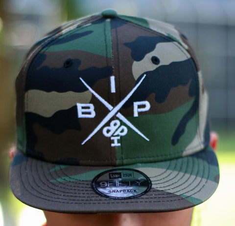 "IBP ""X"" LOGO 2.0 New Era(R) 9FIFTY Ireland Boys Productions (R) Superior New Era 9FIFTY One size fits most. Flat bill adjustable camo cap. This style has an urban attitude thanks to the iconic flat bill and old-school snapback closure. Fabric: 100% cotton."