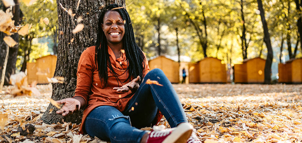 African-American woman sitting on a ground in a public park throwing autumn leaves