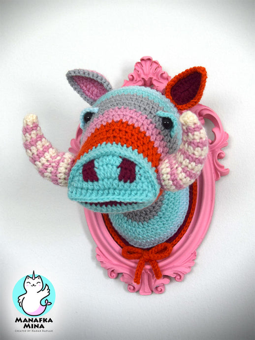 Crochet boar head in a pink frame.