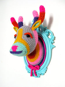 Crochet deer head with in a light turquoise frame.