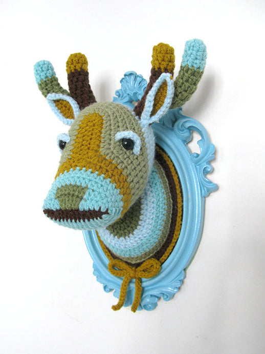 Crochet deer head in a light blue frame.