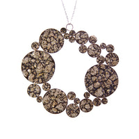 View and buy handmade jewellery by Abby Filer. Image shows a statement necklace made up of multiple sized circles filled with fool's gold affixed into a wider circle attached to a chain.