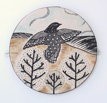 View and buy handmade homeware and wall hangings by Astrid Weigel. Image shows a circular wall canvas printed in a graphic style with a starling flying over a landscape slightly coloured with browns, blue and green.