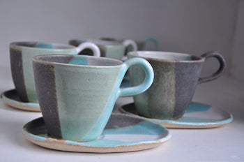 View and buy original handmade homeware by 4 Wheel. Image is of a set of four cup and saucers with a colour-block wash with green, grey and blue.