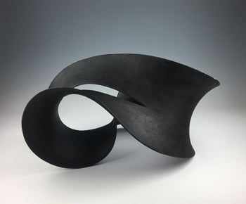 View and buy sculpture by Adrian Bates at The Biscuit Factory. Image shows a black ceramic sculpture which curves like thick ribbon doubling back on itself to create something resembling an infinity symbol.