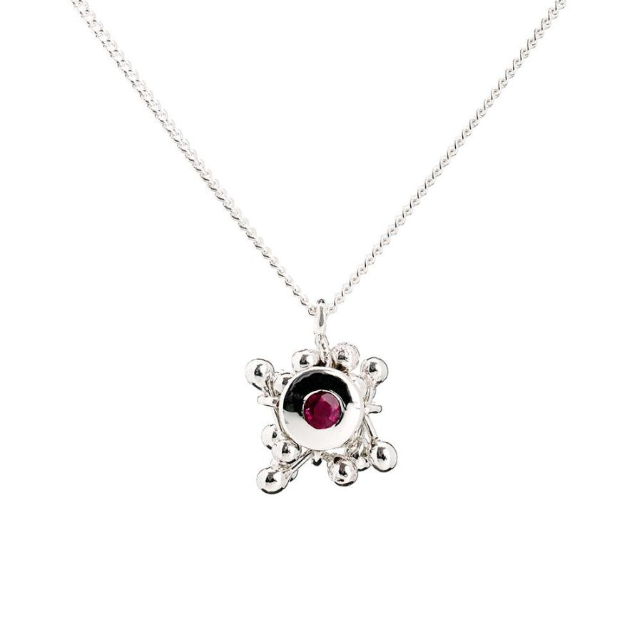 Buy 'Molecule Ruby Cluster Necklace', silver necklace with a precious stone by Yen. Image shows a silver chain dropping into the frame in the shape of a V. From the chain hangs a small ruby stone set in silver and surrounded by a cluster of silver balls. The background is white.