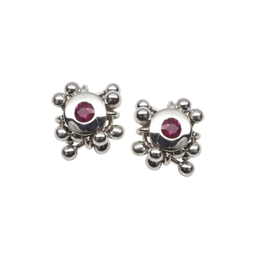 Buy 'Molecule Ruby Cluster Earrings', silver stud earrings with a precious stone by Yen. Image shows 2 earrings sat upright on a white background. A ruby stone is set in silver in each one and surrounded by a cluster of silver balls.