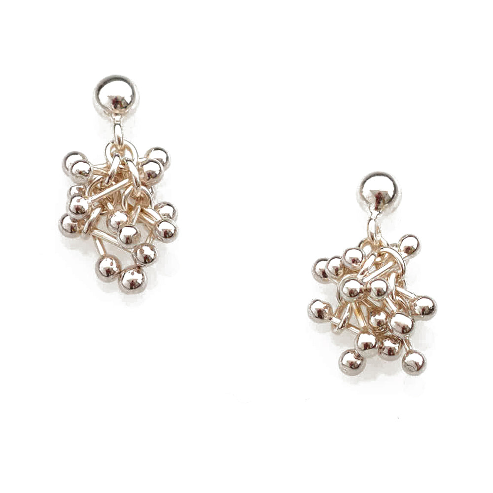 Buy 'Molecule Joy Cluster Studs', silver drop stud earrings by Yen. Image shows a pair of silver drop earrings on a white background. The earrings feature a large silver sphere at the top, hanging from that is a cluster of small bars with silver balls on each end.