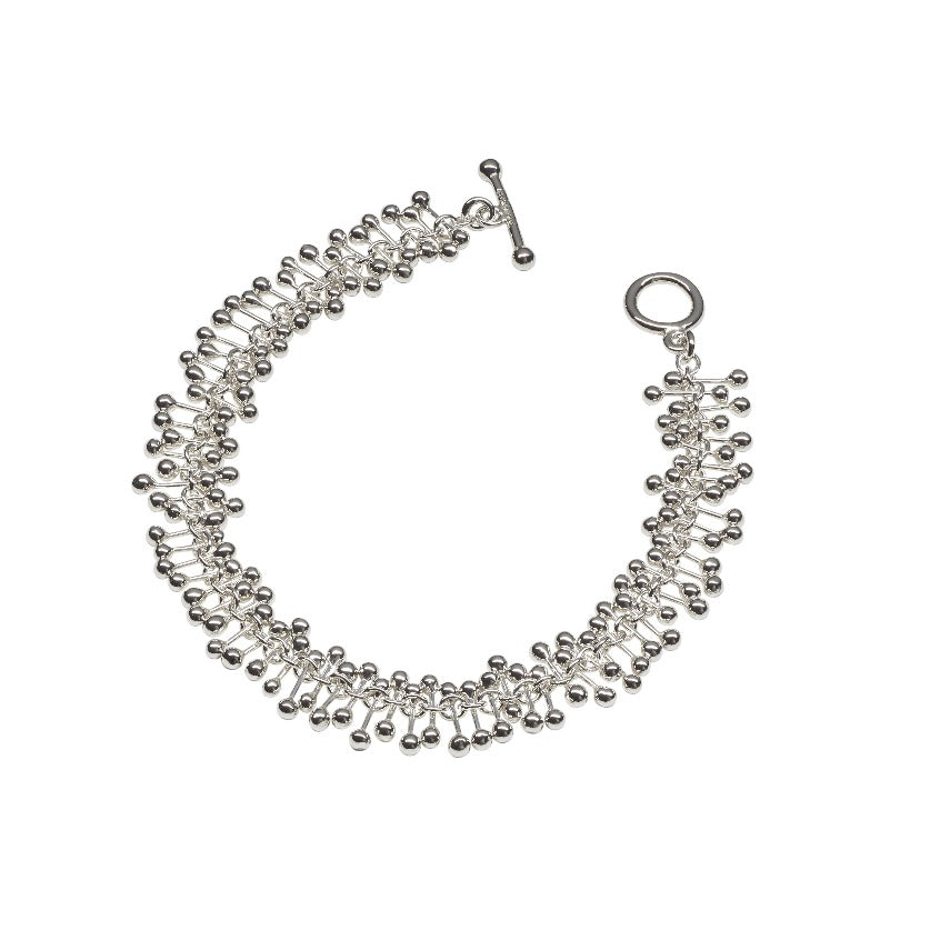 'Molecule Bracelet', silver T-bar bracelet by Yen. Image shows a silver bracelet made up of silver bars fastened to a core chain and fastened with a T-Bar sat on a white background.