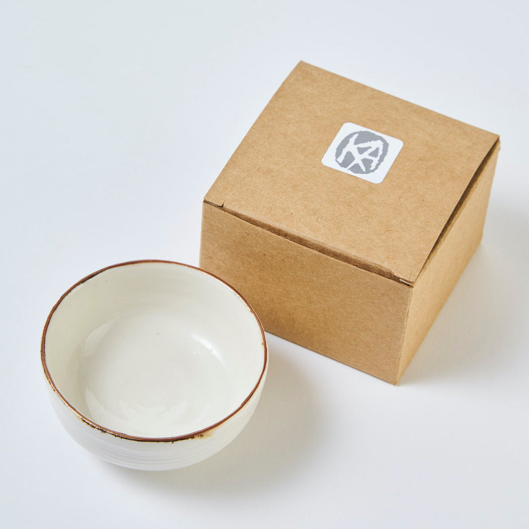 Buy 'Salt Bowl', a small ceramic dish by Kirsty Adams. Image shows a small cream ceramic dish with a bronze rim captured from above. Next to it is a small brown cardboard box branded with a white and grey sticker reading 'KA'. The items are sat on a white background.