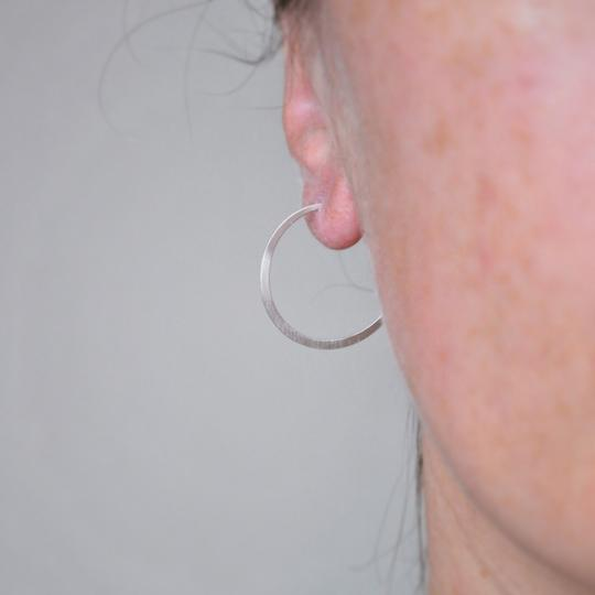 Buy 'Large Silver Hoops' handcrafted jewellery by Sarah Ruth Stanford. Image shows a close up of a person's ear with the rest of the face fading into a blur to the right. In the ear is a simple silver hoop earring. The background is grey