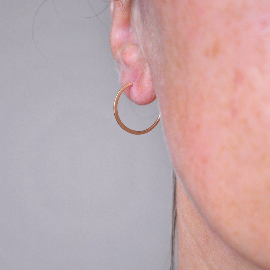 Buy 'Small Gold Hoops' gold earrings by Sarah Ruth Stanford. Image shows a close up of a person's ear with a small gold hoop earring. The background is grey.