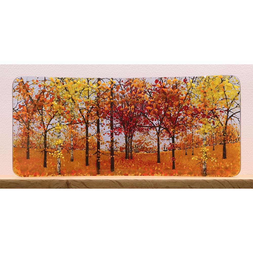 Buy 'Autumn Half Curve' a handmade glass sculpture by Vandacrafts. Image shows a curved glass sculpture depicting an autumnal wood scene, coloured with yellow, red and orange, sitting on a wooden shelf on a white background.