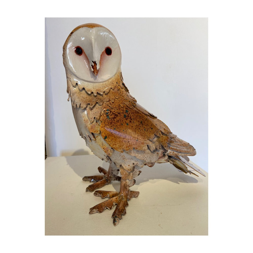 Buy 'Barn Owl' a handmade lacquered steel sculpture by Peter Sales. Image shows a sculpture of a brown and white owl stood at an angle and its face pointed towards the camera. The sculpture sits on a white plinth in front of a white wall.