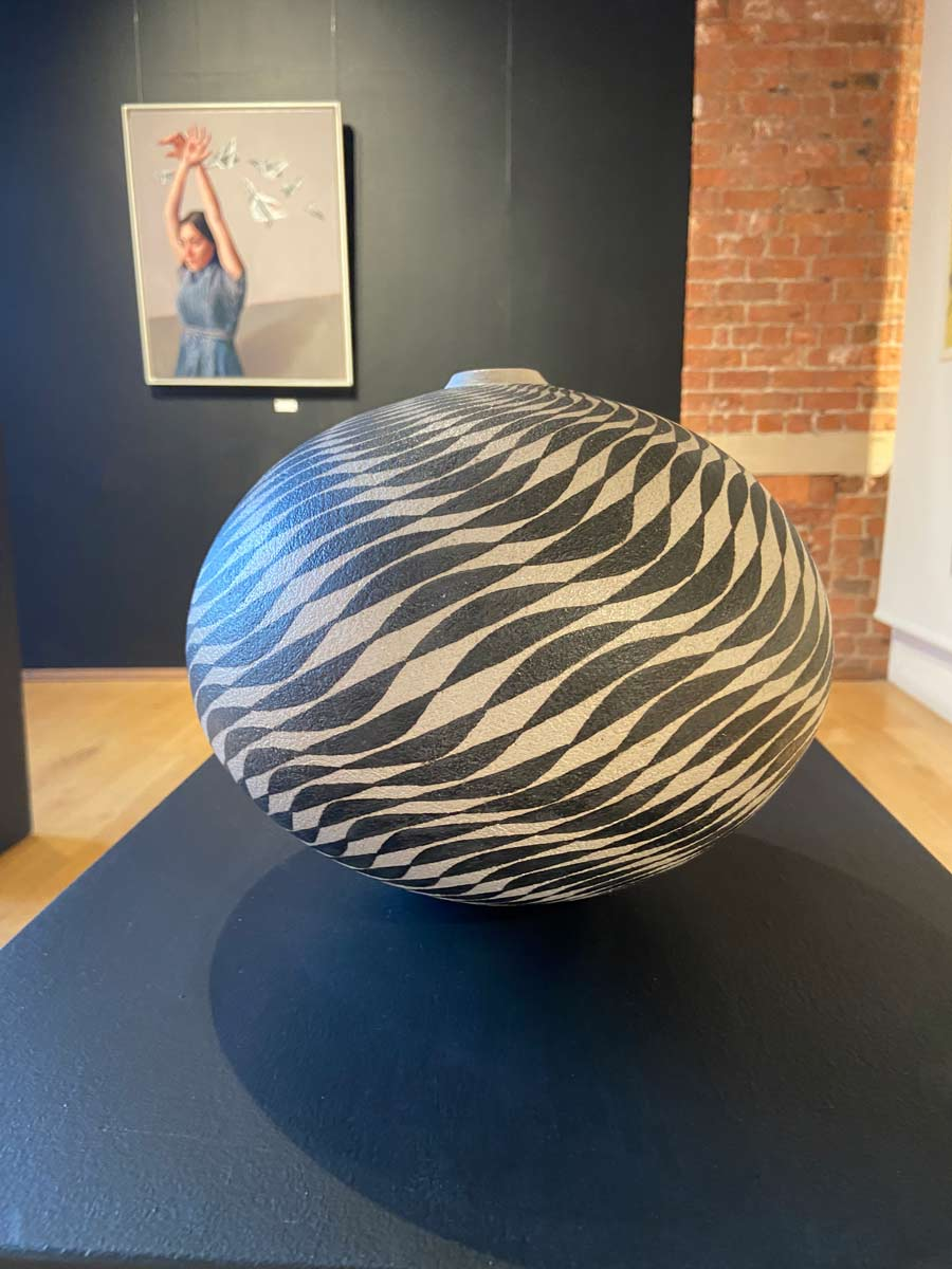 Buy 'Black Waves' a large ceramic vessel by Ilona Sulikova. Image shows a spherical ceramic pot with a very narrow lipped opening at the top decorated with a meticulous black spiraling wave pattern. The pot is sat on a black plinth, in the background there is a black wall with a painting hung up and pine wood flooring.