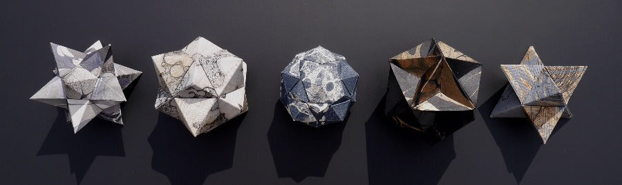 Part of the New Light Exhibition 2020: Buy 'Polyhedral Variations (after Jamnitzer)' a set of wall mounted sculptures by Louisa Boyd. Image shows a set of five wall-mounted geometric sculptures hand marbled in grey and white, orange and black, and blue and white