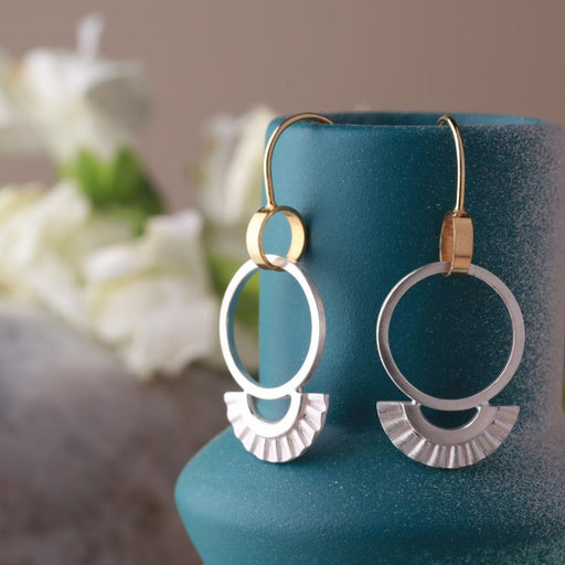 Buy original jewellery online at The Biscuit Factory. 'Sunray Drop Earrings' handmade, two-toned jewellery by Clara Breen. Image shows a pair of earrings made up of gold rings on hooks and a silver circle through the ring with a semi circle of crimped silver at the bottom. The earrings are hooked over a teal vase with flowers blurred in the background.