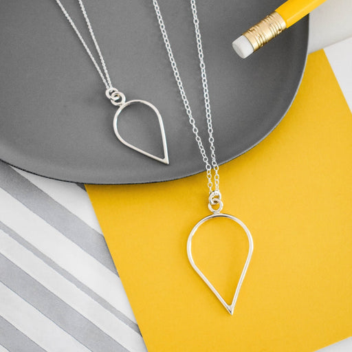 Buy handmade geometric jewellery by Claire Lowe at The Biscuit Factory. Image shows two silver necklaces with a teardrop outline pendant in the same finish sat on a mustard and grey background