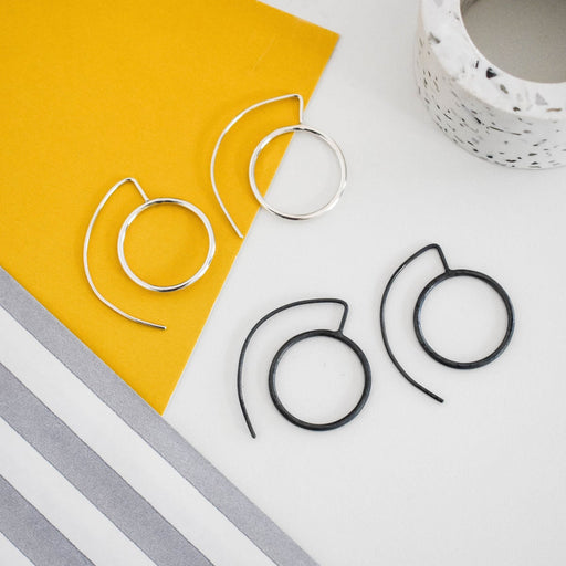 Buy handmade silver geometric jewellery by Claire Lowe at The Biscuit Factory. Image shows two pairs of earrings sat on a mustard and grey background, the earrings are flat circles with an arched wire for threading through the lobe, one oxidised silver and the other polishedsilver