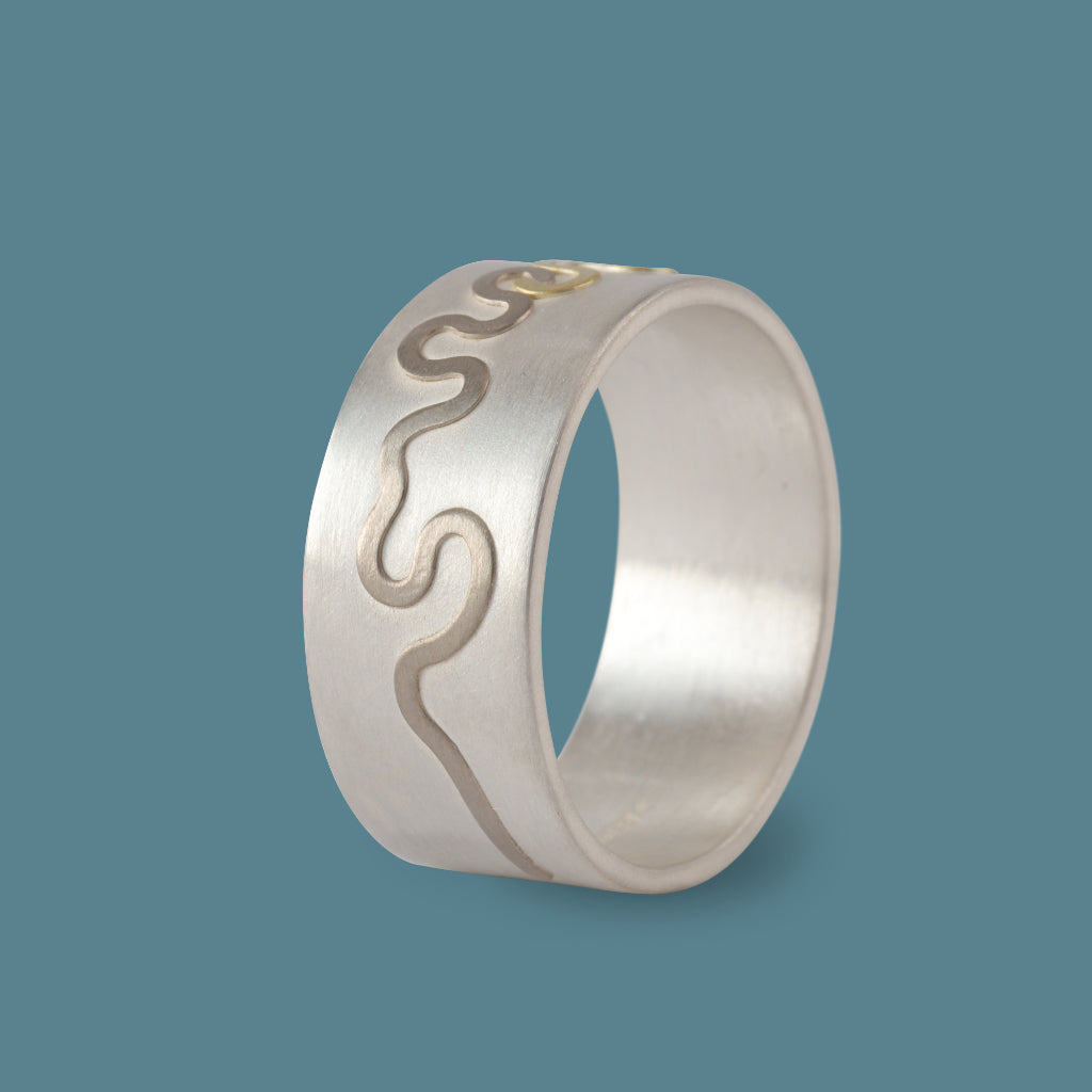 Buy 'River Ring', a silver and gold ring by jewellery designer and maker Clara Breen. Image shows a chunky silver ring decorated with a raised gold and darker silver wavy line around the centre. The ring sits on a blue background.