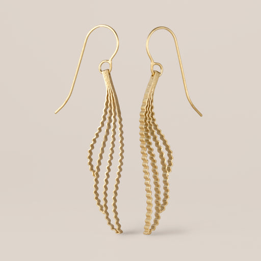 Buy  'Cloud Earrings', gold drop earrings by jewellery designer and maker Clara Breen. Image shows a pair of gold drop earrings with gold crimped waves hanging from gold ear hooks standing upright on a beige background.