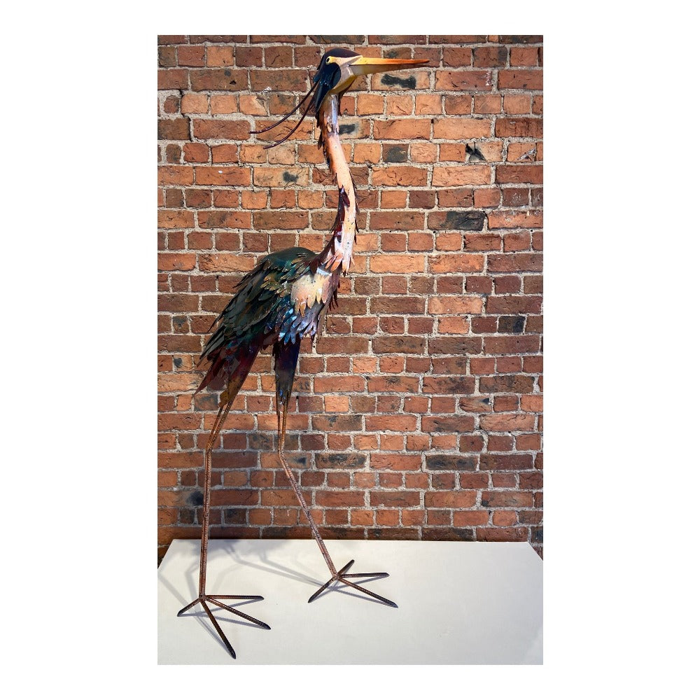 Buy 'Crane' a handmade lacquered steel sculpture by Peter Sales. Images shows a large scale steel sculpture of a crane coloured with gloss brown, teal and yellow paint. The sculpture stands on a white plinth in front of a brick wall.