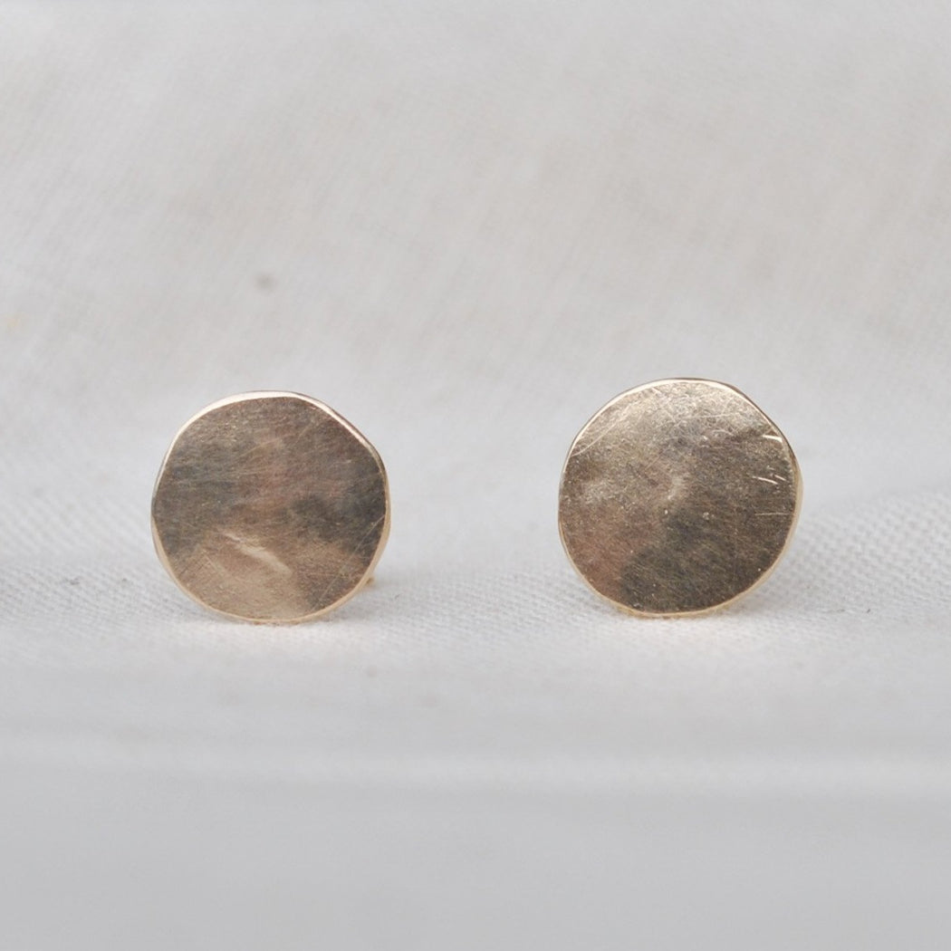 Buy 'Tiny Droplet Studs' recycled gold earrings by Sarah Ruth Stanford. Image shows two subtly bevelled gold discs sat on beige linen side by side.