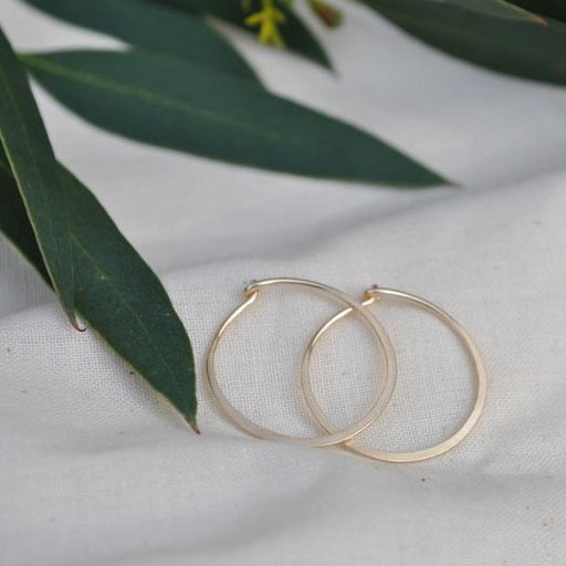 Buy 'Large Gold Hoops' gold earrings by Sarah Ruth Stanford. Image shows a pair of simple gold hoop earrings sat on beige linen with green leaves laying in the background