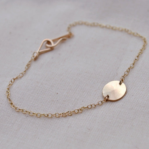 Buy 'Gold Droplet Bracelet' a recycled gold bracelet by Sarah Ruth Stanford. Image shows a bracelet sat on a beige linen background. The bracelet is made up of a gold chain with a subtly bevelled gold disc pendant.