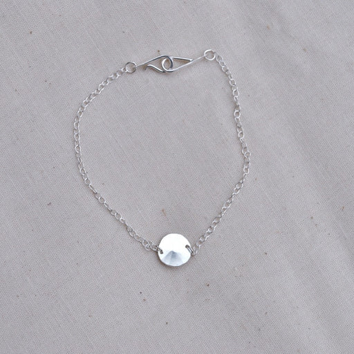 Buy 'Silver Droplet Bracelet' a recycled silver bracelet by Sarah Ruth Stanford. Image shows a bracelet on a beige linen background. The bracelet is made  up of a silver chain and a subtly bevelled silver disc pendant