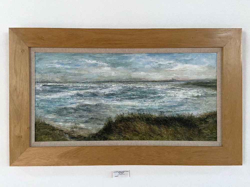 Buy 'Low Newton Beach looking towards Dunstanburgh Castle, Northumberland' a panoramic seascape by Sue Lawson. Image shows a landscape painting of a view across the sea with a grassy knoll cliff in the foreground and small silhouetted castle in the background. The painting is displayed in an oak frame with a linen mount on a white wall.