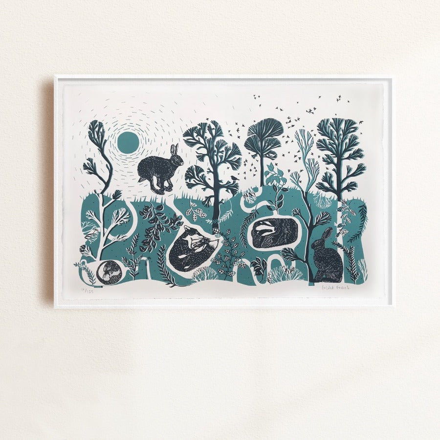 Buy 'Leaping Hare' a landscape animal print by Folded Forest. Image shows a teal, white and black screen print featuring a stylised landscape with a hare, a badger and a fox. The print is displayed in a white frame hung on a white wall.