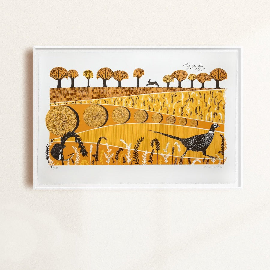 Buy 'Pheasant' a landscape animal print by Folded Forest. Image shows a screenprint in yellow, orange and brown featuring patterned fields and trees with a pheasant in the foreground and a hare in the background. The print is displayed in a white frame and hung on a white wall.